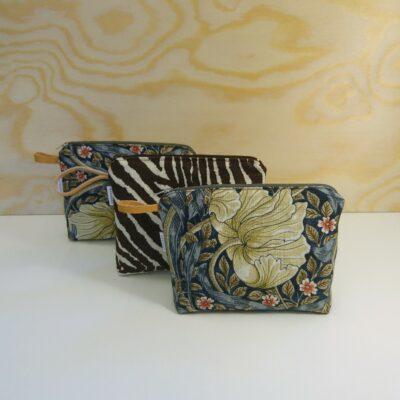 Fodrade necessärer i linne, klassiska mönster från Morris & Co och Brunschwig & Fils. Detalj i naturgarvat läder från Tärnsjö garveri. Tillverkning och form: Svängen. Pris: 350:-